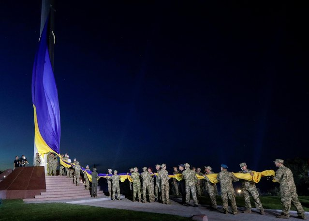 Ukrainian veterans attend a raising ceremony of the biggest national flag on the country's highest flagpole to mark the Day of the National Flag in Kyiv, Ukraine on August 22, 2020. (Photo by Valentyn Ogirenko/Reuters)