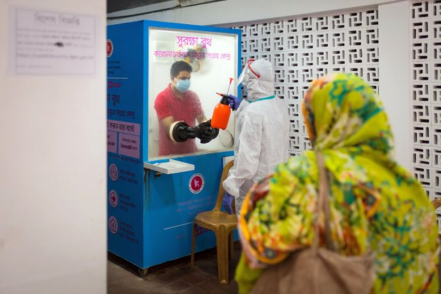A woman is waiting in front of a COVID 19 test sample collection booth while medical employees are preparing the booth and disinfecting the area in Dhaka, Bangladesh, on September 15, 202. Bangladesh confirmed cases of COVID- 19 is 339,332 and death 4759 on September 15, 2020. (Photo by Istiak Karim/NurPhoto via Getty Images)