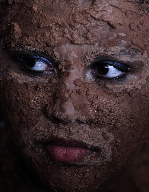 A woman caked in mud takes part in a presentation during the inauguration of the National Meeting of Rural Women in Brasilia, on February 18, 2013. (Photo by Eraldo Peres/Associated Press)