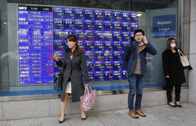 A man uses a mobile phone in front of an electronic stock indicator of a securities firm in Tokyo, Thursday, November 20, 2014. Asian stocks faltered Thursday as China's manufacturing weakened and the latest Fed minutes reminded investors that U.S. interest rates are likely to rise next year. Japan's Nikkei 225 closed at 17,300.86 Thursday. (Photo by Shizuo Kambayashi/AP Photo)