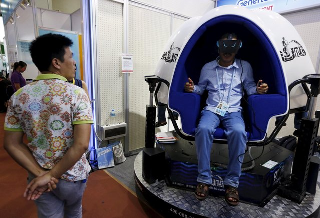 A foreign visitor tries a virtual reality product during the China Import and Export Fair, also known as Canton Fair, in the southern Chinese city of Guangzhou October 15, 2015. (Photo by Bobby Yip/Reuters)