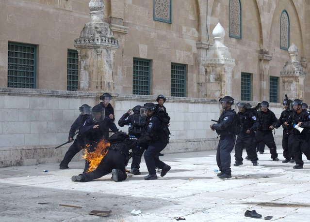 Israeli riot policemen help a comrade after a fire bomb was thrown at him during clashes with Palestinian demonstrators at Jerusalem's al-Aqsa mosque compound following Friday prayers on March 8, 2013. Palestinians enraged by reports that an Israeli policeman mishandled a Koran battled riot officers at Jerusalem's Al-Aqsa mosque compound with stones and petrol bombs, police and witnesses said. (Photo by STR/AFP Photo)
