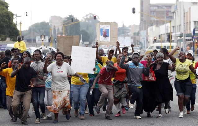 Protesters chant slogans as they celebrate after nine South African policemen accused of murder were denied bail at the Benoni court, east of Johannesburg, March 12, 2013. The nine South African policemen charged with the murder of a Mozambican taxi driver who was shackled to the back of a police vehicle and dragged to a nearby station were denied bail on Tuesday. The police officers have pleaded not guilty to murder but cellphone footage captured by an onlooker and broadcast around the world by news channels shows heavy-handed treatment meted out to 27-year-old Mido Macia. (Photo by Siphiwe Sibeko/Reuters)