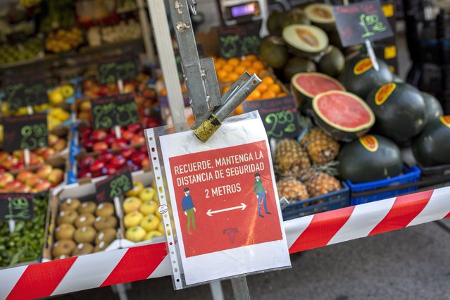 "A sign of social distancing guidelines hangs on a street stall in a market in Madrid, Spain, Tuesday, October 13, 2020. The sign reads in Spanish ""Remember, keep a safe distance 2 meters"". (Photo by Bernat Armangue/AP Photo)"