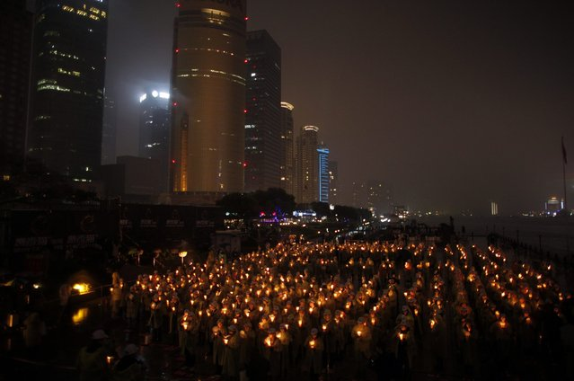 """People hold candles during an event attempting to establish a Guinness World of Record for """"Blowing out the most number of candles simultaneously"""" during Earth Hour in Shanghai March 23, 2013. Earth Hour, when everyone around the world is asked to turn off lights for an hour from 8.30 p.m. local time, is meant as a show of support for tougher action to confront climate change. (Photo by Carlos Barria/Reuters)"""