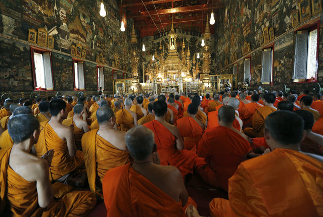 Thai Buddhists monks pray in front of the Emerald Buddha (C) during the ceremony on the occasion of Thai King Bhumibol Adulyadej's 87th Birthday anniversary at the Royal Palace compound in Bangkok, Thailand, December 4, 2014. Thousands of Thai Buddhists are to join the prayer ceremony for the world's longest serving monarch on December 5. (Photo by Narong Sangnak/EPA)