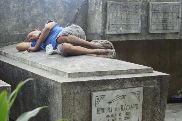 A man sleeps on top of a grave inside a public cemetery in Makati financial district of Manila October 31, 2015. Filipinos flock to cemeteries across the country to commemorate their departed loved ones for All Saints and All Souls Days, which fall on November 1 and 2 respectively. (Photo by Janis Alano/Reuters)