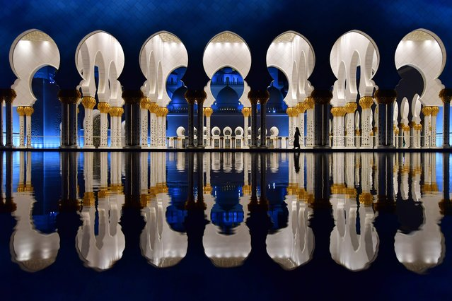 A picture taken on December 3, 2017 shows visitors walking in the courtyard of the Sheikh Zayed Grand Mosque in the UAE capital Abu Dhabi. (Photo by Giuseppe Cacace/AFP Photo)