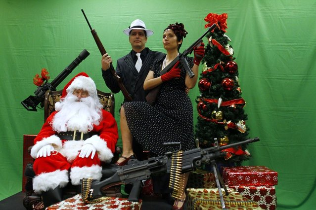 Todd Engle (C) and Mary Rose Engle (R) hold weapons as they pose for a photograph with a man dressed as Santa Claus at the Scottsdale Gun Club in Scottsdale, Arizona December 10, 2011. (Photo by Joshua Lott/Reuters)