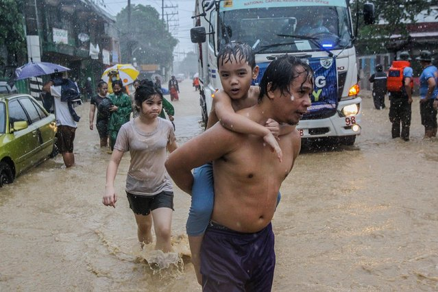 Residents wade through the flood brought by typhoon Vamco in Manila, the Philippines, on November 12, 2020. Typhoon Vamco, the third powerful cyclone to batter the Philippines in 11 days, made landfall on Wednesday night, unleashed fierce winds and intense rains that triggered landslide, rockslide and flash floods. (Photo by Rouelle Umali/Xinhua News Agency)