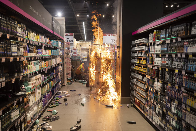 A fire set by protesters burns inside a Carrefour supermarket during a protest against the murder of Black man Joao Alberto Silveira Freitas at a different Carrefour supermarket the night before, on Brazil's National Black Consciousness Day in Sao Paulo, Brazil, Friday, November 20, 2020. (Photo by Andre Penner/AP Photo)