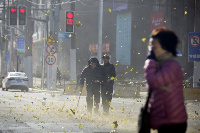 People walk along a street on a windy day in central Shanghai, December 16, 2014. (Photo by Aly Song/Reuters)