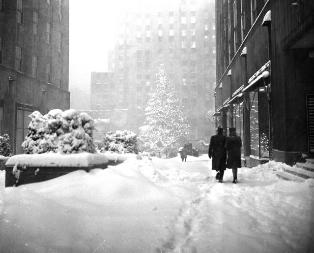 The landmark Christmas tree at New York's Rockefeller Plaza stands out December 26, 1947 as a few hardy pedestrians make their way through the snow drifts of one of the heaviest winter storms in years. (Photo by Harry Harris/AP Photo)