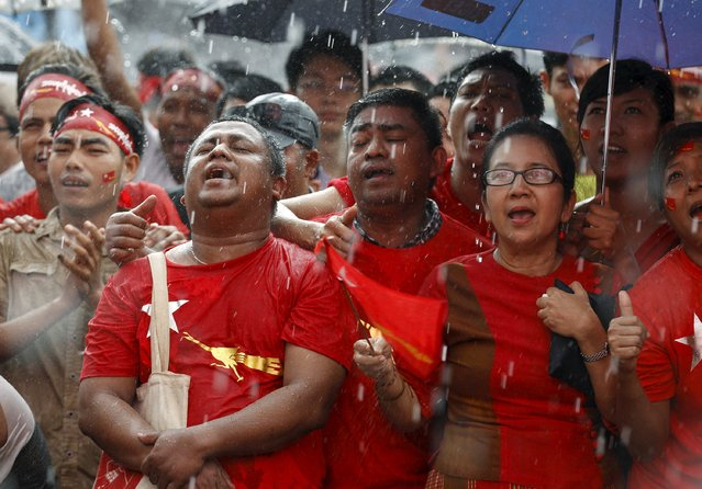 Supporters sing a song for Myanmar pro-democracy leader Aung San Suu Kyi as they wait for official results from the Union Election Commission during heavy rain fall in front of National League for Democracy Party (NLD) head office at Yangon, November 9, 2015. (Photo by Soe Zeya Tun/Reuters)