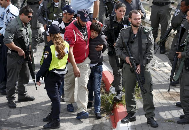 Israeli police lead away a Palestinian minor (C) they said stabbed an Israeli security guard in Pisgat Zeev, which lies on occupied land that Israel annexed to Jerusalem after the 1967 Middle East war, November 10, 2015.  An Israeli police spokeswoman said two Palestinians, who she said were aged 12 to 13, stabbed a security guard on the Jerusalem light-rail train in Pisgat Zeev, a Jewish settlement north of Jerusalem. The guard shot back at them wounding one. (Photo by Ammar Awad/Reuters)