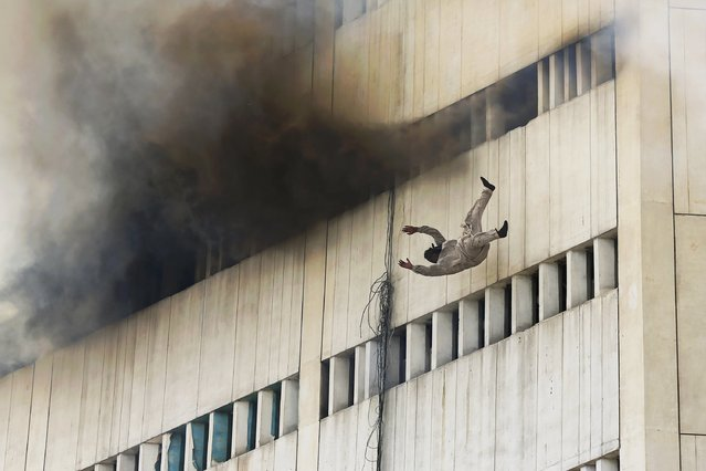 A man falls from a high floor of a burning building in central Lahore May 9, 2013. Fire erupted on the seventh floor of the LDA plaza in Lahore and quickly spread to higher floors leaving many people trapped inside the building. At least three people fell from the high floors trying to avoid fire that engulfed the building, local media reports. (Photo by Damir Sagolj/Reuters)