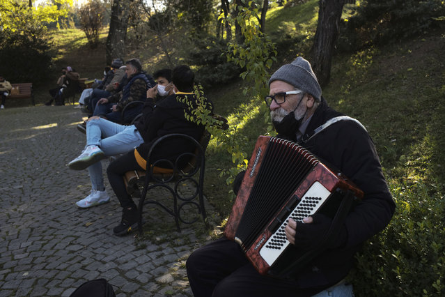 A musician performs in a public garden, in Ankara, Turkey, Friday, November 27, 2020. When Turkey changed the way it reports daily COVID-19 infections, it confirmed what medical groups and opposition parties have long suspected – that the country is faced with an alarming surge of cases that is fast exhausting the Turkish health system. The official daily COVID-19 deaths have also steadily risen to record numbers in a reversal of fortune for the country that had been praised for managing to keep fatalities low. With the new data, the country jumped from being one of the least-affected countries in Europe to one of the worst-hit. (Photo by Burhan Ozbilici/AP Photo)