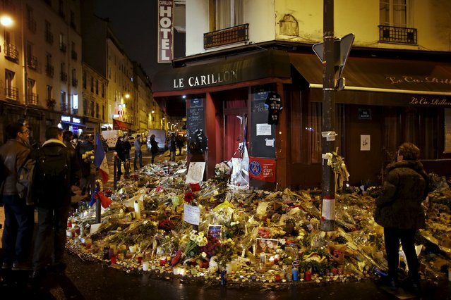 """People mourn outside """"Le Petit Cambodge"""" and """"Le Carillon"""" restaurants a week after a series of deadly attacks in the French capital, in Paris, France, November 20, 2015. (Photo by Benoit Tessier/Reuters)"""