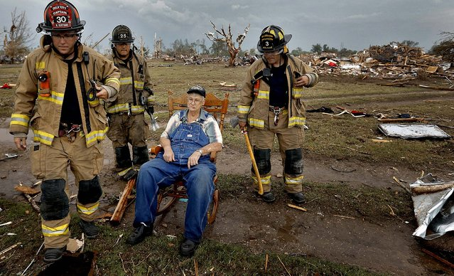 Oklahoma City firefighters check on the status of Gene Tripp as he sits in his rocking chair where his home once stood, in Oklahoma City. (Photo by Chris Landsberger/The Oklahoman)
