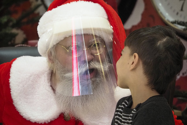 An actor dressed as Santa Claus and wearing a face mask to protect against coronavirus infection speaks with a boy during the New Year celebration in a shopping mall in St.Petersburg, Russia, Saturday, January 2, 2021. (Photo by Dmitri Lovetsky/AP Photo)