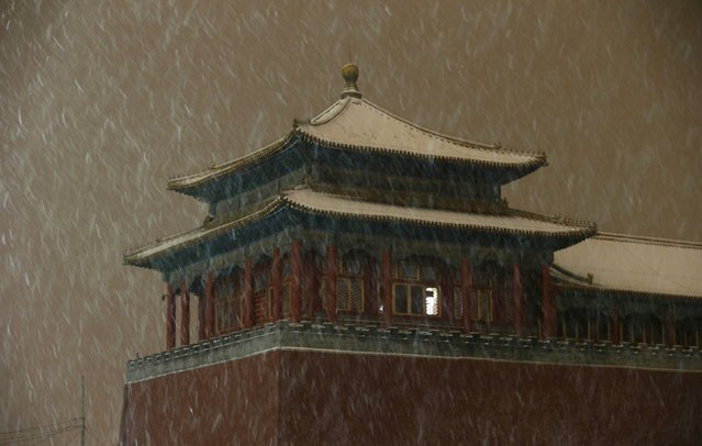Snow falls on a tower of the Wumen Gate at the Forbidden City, at night in central Beijing, China, November 22, 2015. (Photo by Jason Lee/Reuters)