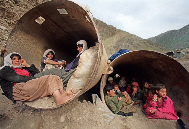 """Iraqi Kurdish refugees seek shelter 16 April 1991 in public works tubing near Chouchani. Iraqi Kurdish families are fleeing from their homes to the """"safety"""" of the mountains along the Turkish-Iraqi and Iranian borders, with little to protect them from the cold as fighting intensifies between Saddam Hussein' soldiers and the Kurdish peshmerga guerrillas. Several thousand British, American and French troops moved 22 April into northern Iraq to prepare camps as part of operation """"Provide Comfort"""" for the 500,000 Kurdish refugees. (Photo by Joel Robine/AFP Photo)"""