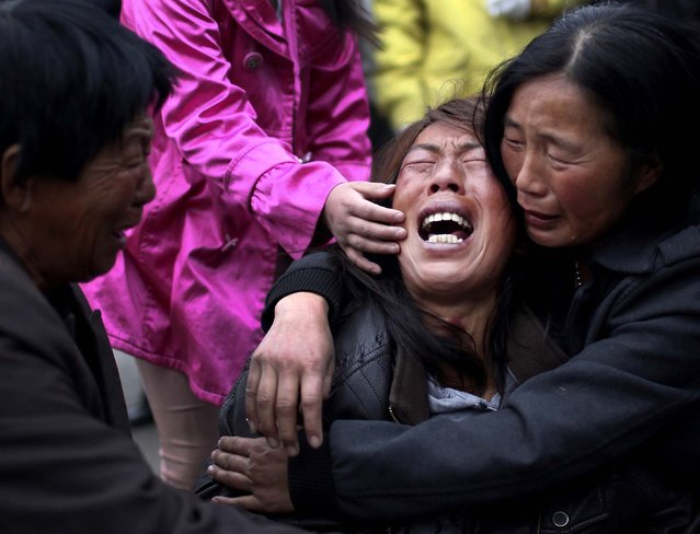 A family member of a worker cries near the accident site of Monday's fire at a poultry processing workshop in Dehui City, China, on June 4, 2013. The swift-moving fire trapped panicked workers inside the poultry slaughterhouse that had only a single open exit, killing at least 119 people in one of the country's worst industrial disasters in years. (Photo by Jin Liwang/Xinhua)