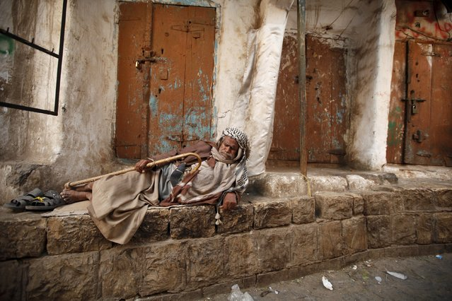 A homeless man rests on the side of a street at the old quarter of Yemen's capital Sanaa November 27, 2015. (Photo by Khaled Abdullah/Reuters)