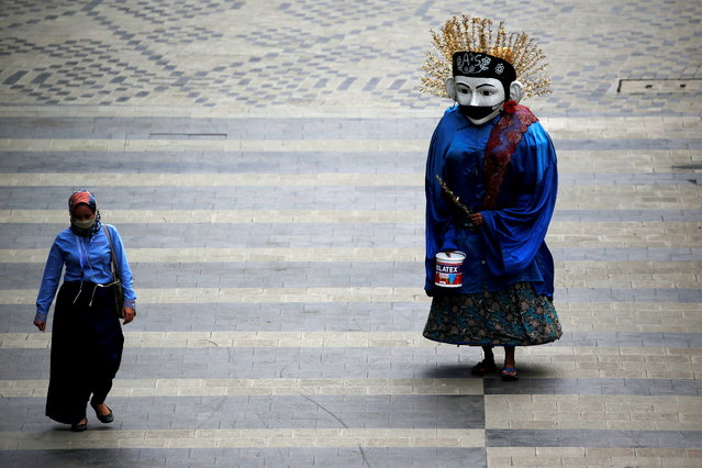 """A traditional large puppet figure known as """"Ondel-ondel"""", wearing a face mask, performs on a sidewalk of the main road, as the outbreak of the coronavirus disease (COVID-19) continues in Jakarta, Indonesia, January 4, 2021. (Photo by Willy Kurniawan/Reuters)"""