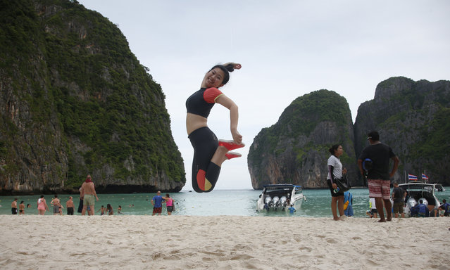 A tourist jumps for a photo on the popular on Maya Bay on Phi Phi island in Krabi province, Thailand, Thursday, May 31, 2018. Maya Bay on Phi Phi Leh Island in the Andaman Sea will close to tourists for four months from Friday to give its coral reefs and sea life a chance to recover from an onslaught that began nearly two decades ago. (Photo by Sakchai Lalit/AP Photo)
