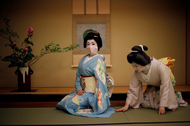 """Mayu adjusts Koiku's kimono, as Koiku wears a protective face mask while posing for a photograph, before they work at a party where they will entertain with other geisha at Japanese luxury restaurant Asada in Tokyo, Japan, June 23, 2020. The coronavirus pandemic has made Tokyo's geisha fear for their centuries-old profession as never before. Though the number of geisha - famed for their witty conversation, beauty and skill at traditional arts - has been falling for years, they were without work for months due to Japan's state of emergency and now operate under awkward social distancing rules. Engagements are down 95 percent, and come with new rules: no pouring drinks for customers or touching them even to shake hands, and sitting 2 meters apart. Masks are hard to wear with their elaborate wigs, so they mostly don't. """"I was just full of anxiety"""", said Mayu, 47. """"I went through my photos, sorted my kimonos ... The thought of a second wave is terrifying"""". (Photo by Kim Kyung-Hoon/Reuters)"""