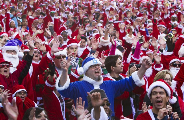 """Runners dressed as Santa Claus, including """"Jewish Santa"""" Seth Balaban (C), gather for the 11th annual Las Vegas Great Santa Run in downtown Las Vegas, Nevada, December 5, 2015. The Las Vegas run competes with a run in Liverpool, England to see who can gather the largest number of Santas. (Photo by Steve Marcus/Reuters)"""