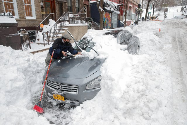 A man removes snow from a car during a snowstorm in the Brooklyn borough of New York City, New York, U.S., February 2, 2021. (Photo by Brendan McDermid/Reuters)