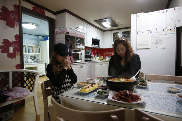 Kim Si-yoon and her mother pray before dinner at their house in Seoul December 16, 2014. (Photo by Kim Hong-Ji/Reuters)