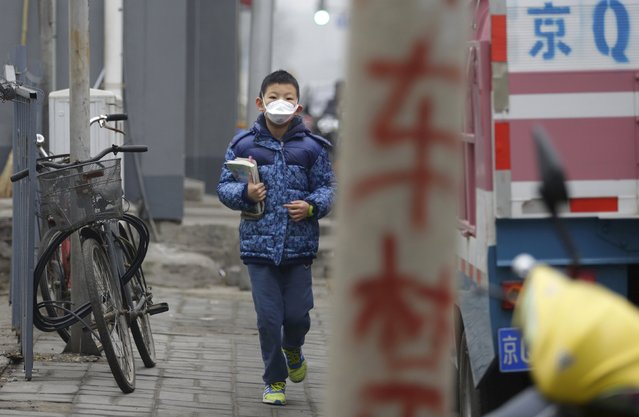 "A primary school student wearing a mask walks along a street with his textbooks amid heavy smog after his school was closed due to the first ever ""red alert"" for air pollution, in central Beijing, China, December 8, 2015. (Photo by Jason Lee/Reuters)"