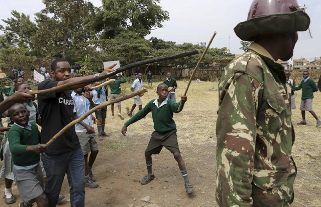 Kenyan school pupils and activists challenge riot police during a protest against the removal of their school's playground, at the Langata Road Primary School, in Nairobi, Kenya Monday, January 19, 2015. Kenyan police tear-gassed schoolchildren demonstrating against the removal of their school's playground, the land of which has been allegedly grabbed by a powerful politician, according to a Kenyan human rights activist. (Photo by Brian Inganga/AP Photo)