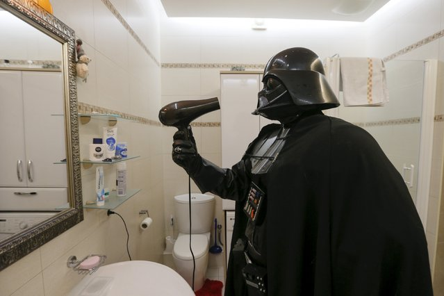 Darth Mykolaiovych Vader, who is dressed as the 'Star Wars' character Darth Vader, poses for a picture as he dries his mask and helmet with a hairdryer in the bathroom of his apartments in Odessa, Ukraine, December 2, 2015. (Photo by Valentyn Ogirenko/Reuters)