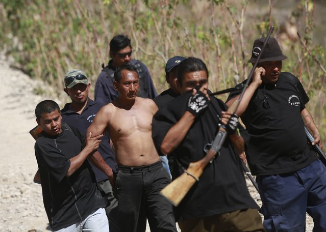 Members of the Community Police of the FUSDEG (United Front for the Security and Development of the State of Guerrero) walk with a man that they captured after a shootout against a group, that villagers suspect are members of a local gang, at a hill in the village of Petaquillas, on the outskirts of Chilpancingo, in the Mexican state of Guerrero, February 1, 2015. (Photo by Jorge Dan Lopez/Reuters)