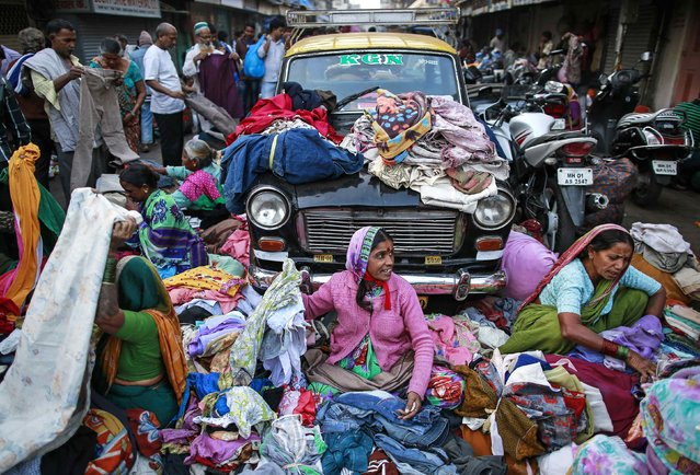 Vendors sell clothes on the roadside at a second-hand street side clothing market in Mumbai January 28, 2015. (Photo by Danish Siddiqui/Reuters)
