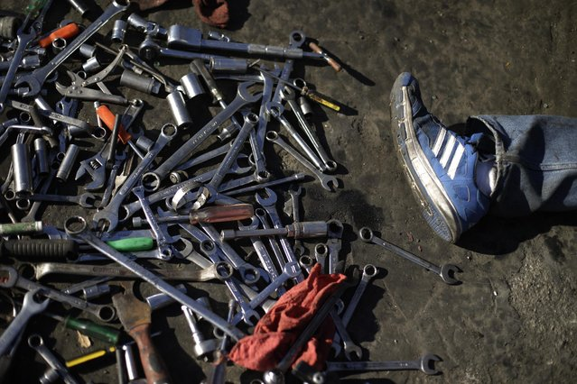 In this Wednesday, November 11, 2015 photo, tools are seen scattered on the yard as a customer pulls some parts from a junk car at Aadlen Brothers Auto Wrecking, also known as U Pick Parts, in the Sun Valley section of Los Angeles. (Photo by Jae C. Hong/AP Photo)
