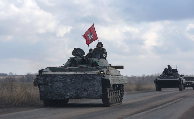 Members of the separatist self-proclaimed Donetsk People's Republic drive armoured vehicles, with Saint George slaying the Dragon displayed on a red flag, near Yenakiieve, Donetsk region, February 4, 2015. The coat of arms of the Russian capital Moscow depicts St. George the Victorious atop a silver horse slaying a black dragon with silver harness, according to the official web site of Moscow city government. (Photo by Maxim Shemetov/Reuters)