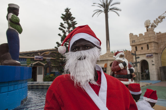 In this photo taken Saturday, December 19, 2015, Mamadou Ngueye, who dresses as Santa Claus waits for a guest to take a picture with at the amusement park  Darkar, Senegal. Ngueye, is one of many Pere Noels, or Father Christmases, seen in Senegal's capital this festive season. He, like the majority of Senegalese, is Muslim and yet celebrates Christmas. (Photo by Jane Hahn/AP Photo)