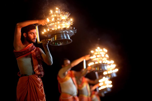 """Hindu priests perform """"Narmada Aarti"""" or the worshipping of Narmada river which is considered sacred, at Jabalpur, some 300km from the state capital Bhopal, India, 18 March 2021. Everyday, thousands of devotees attend the Narmada Aarti at the banks of river Narmada as a ritual. (Photo by Sanjeev Gupta/EPA/EFE)"""