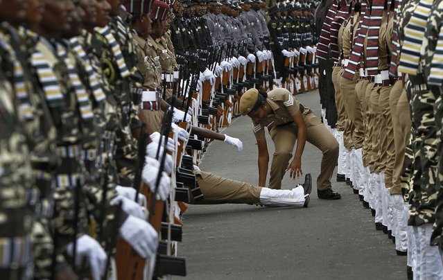 An Indian policewoman helps her comrade who fainted during the full-dress rehearsal for India's Independence Day celebrations in Chennai, on August 13, 2013. India commemorates its Independence Day on August 15. (Photo by Babu/Reuters)