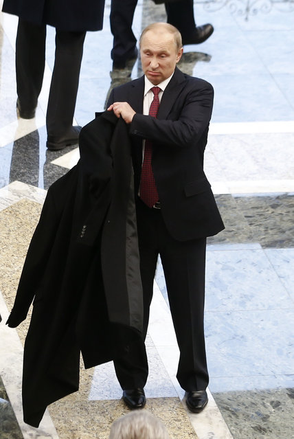 Russian President Vladimir Putin puts on his coat after peace talks on resolving the Ukrainian crisis in Minsk, February 12, 2015. The leaders of Germany, France, Russia and Ukraine have agreed a deal to end fighting in eastern Ukraine, participants at the summit talks said on Thursday. (Photo by Vasily Fedosenko/Reuters)