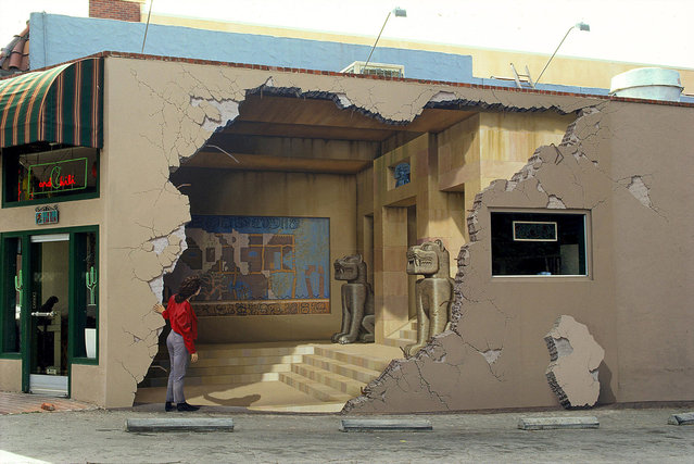 """Siete Punto Uno (7.1) 16' x 24' in Los Gatos, California, undated. Artist John Pugh is used to people's amazed reactions when they pass his epic architectural murals. John is a trompe l'oeil artist (trick of the eye) meaning he paints incredibly realistic scenes that delude the viewer into a seeing a 3D scene painted on a flat surface. """"They say 'wow did you see that. I thought that was real"""", said John, from California who works on a large scale on public and residential areas. """"These life-size illusions allow me to communicate with a very large audience. It seems almost universal that people take delight in being visually tricked"""". John's works can be seen all over the world from New Zealand to Hawaii and each piece tells a story of the area they are positioned. (Photo by John Pugh/Barcroft Media/Getty Images)"""