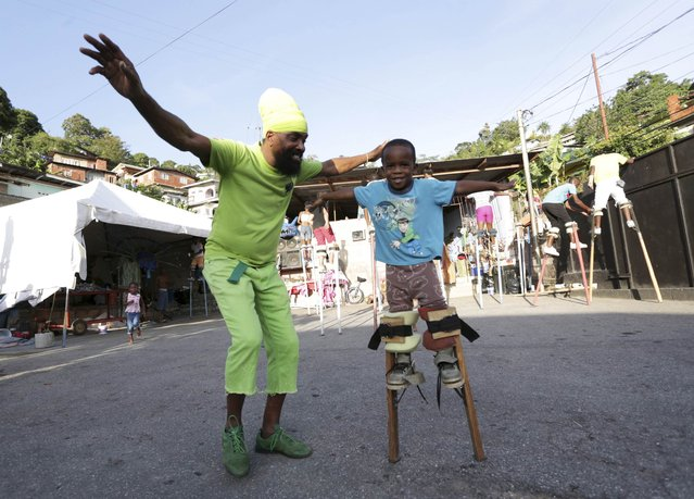 "Keylemanjahro founder, Glenn ""Dragon"" De Souza, teaches a young stilt walker, Mojah Harding, how to maintain his balance as he walks on stilts in the yard at Harding Place, Cocorite, just West of the capital of Port-of-Spain, Trinidad, on February 8, 2015. (Photo by Andrea De Silva/Reuters)"