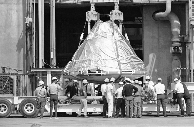 Technicians and officials inspect the aluminum covered Apollo 1 spacecraft after it was lowered from its booster at pad 34 at Cape Kennedy, Florida on February 17, 1967. Astronauts Virgil Grissom, Edward White and Roger Chaffee, lost their lives when a flash fire raced through the spacecraft on January 27. For the next several days the vehicle will be examined in detail by investigators probing to find out what caused the tragedy. (Photo by Jim Kerlin/AP Photo/Pool)