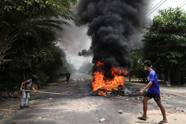 """An anti-coup protester walks past burning tires after activists launched a """"garbage strike"""" against the military rule, in Yangon, Myanmar, March 30, 2021. (Photo by Reuters/Stringer)"""