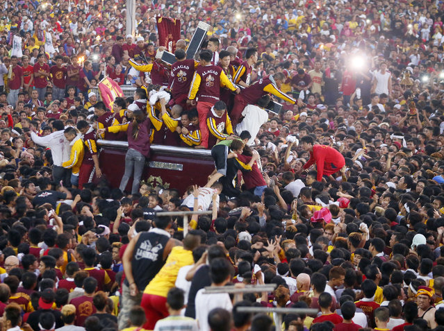 Tens of thousands of Catholic devotees jostle to get closer to the image of the Black Nazarene as they take part in a raucous procession to celebrate its feast day in Manila, Philippines, Saturday, January 9, 2016. As in the past, the annual procession attracts thousands of devotees with scores being injured and saw the deployment of hundreds of police and soldiers. (Photo by Bullit Marquez/AP Photo)